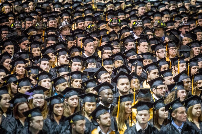 A sea of faces in graduation caps and gowns