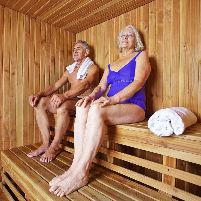 Deux personnes âgées assises dans un sauna en bois, les yeux fermés.