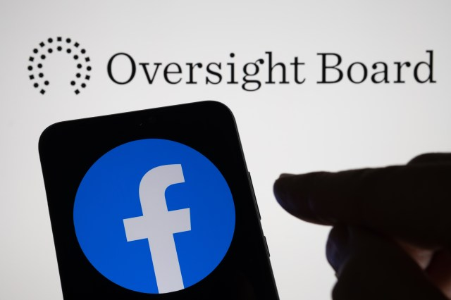 The oversight board's logo behind a phone screen with the Facebook icon