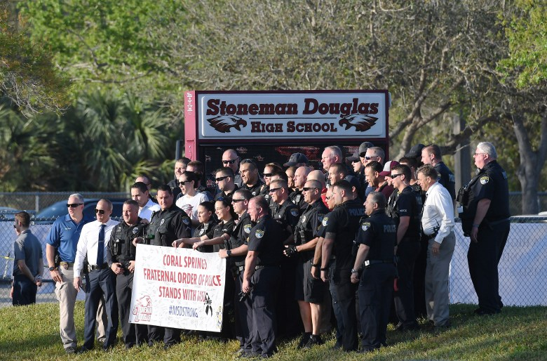 Group of uniformed police stand with a sign welcoming back students in front of the school, on a sunny day