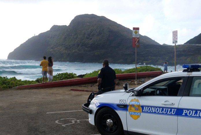 Police car from Honolulu police parked in a parking lot near the beach with an officer standing in front of it; in the backgroundn a couple looks out at the ocean
