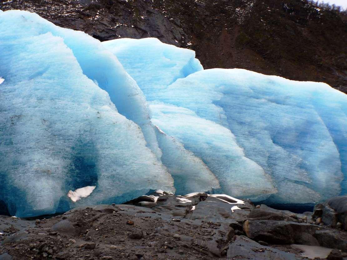 Bright blue glacier ice on rocky terrain.