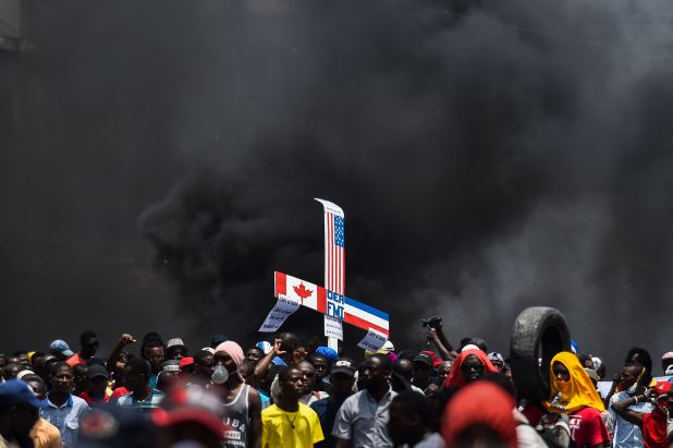 Crowd in the street under smoky skies hold up a sign with U.S., Canadian and other foreign flags