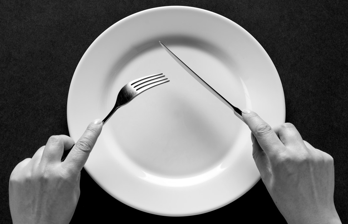 An image of two hands holding a knife and fork over an empty plate.
