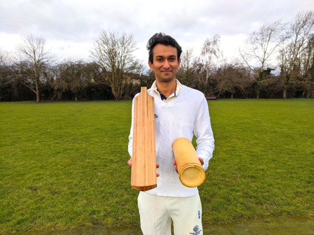 A man in cricketing clothes holds a bat and a piece of bamboo