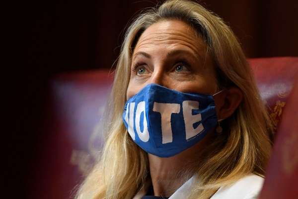 A woman looking up wearing a blue mask with the word 'VOTE' on it. domestic violence