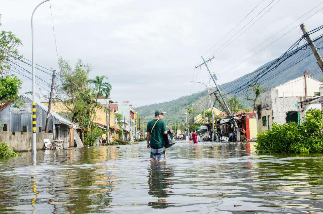 Man walks through flooded street
