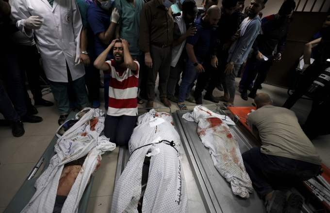 A man in grief on his knees next to the bodies of three of his family members laid out on stretchers.