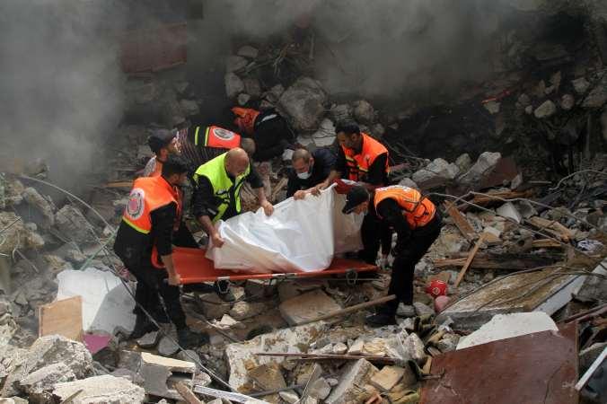 Palestinian civil defense members rescue a man.