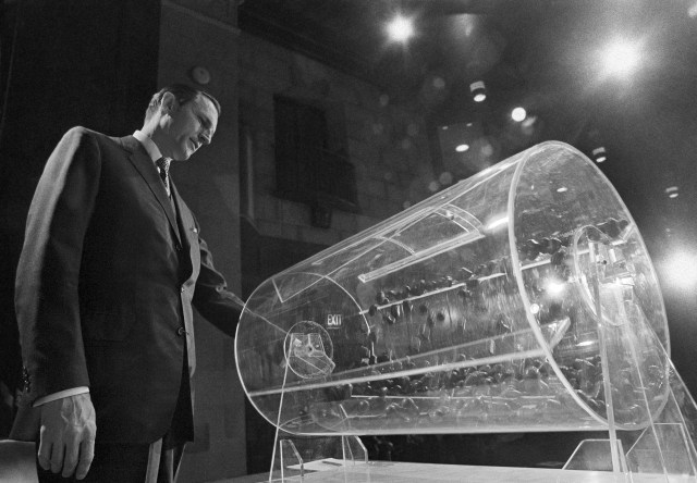 A man stands in front of a clear plastic cylinder containing tokens