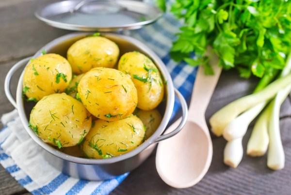 A bowl of boiled potatoes with fresh dill on top.