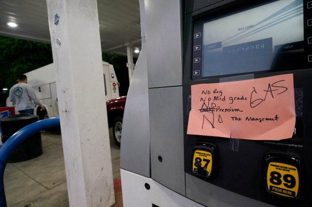 A handwritten sign posted on a gas pump showing that the service station is out of all grades of fuel