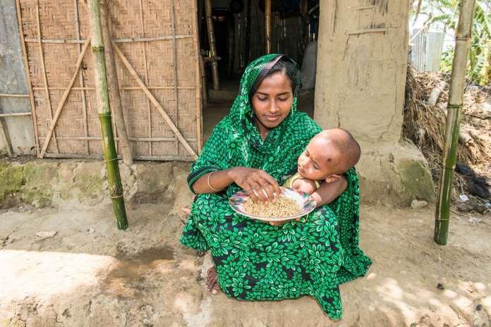 Woman sitting outside a hut, holding small child