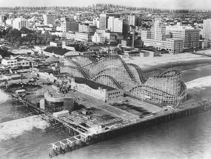 An old black-and-white photo of a roller coaster on a pier, with the city behind it and then a long row of oil derricks behind that on a ridge.