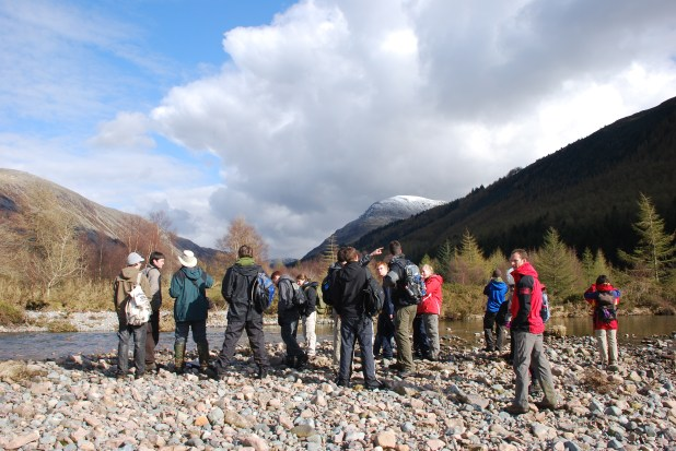 A group of people standing in a valley bottom surrounded by trees and hills.