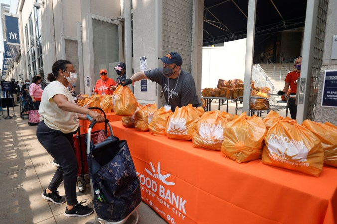 New York residents line up to receive food items at a food bank.