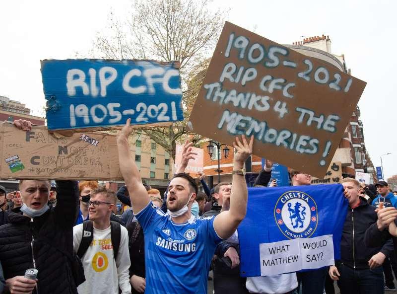 Chelsea fans holding anti-Super League placards.
