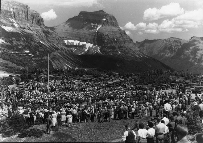 Crowds at a ceremony with mountains in the background.
