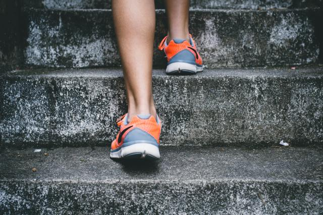 Legs of someone wearing orange and gray shoes walking up concrete steps.