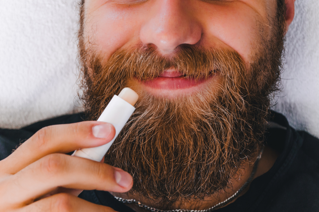 Man with beard applying lip balm