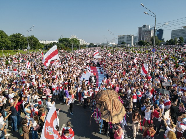 Huge crowds waving red-and-white flags in a public square