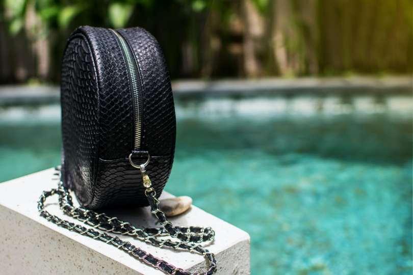 Snakeshin bag next to a swimming pool
