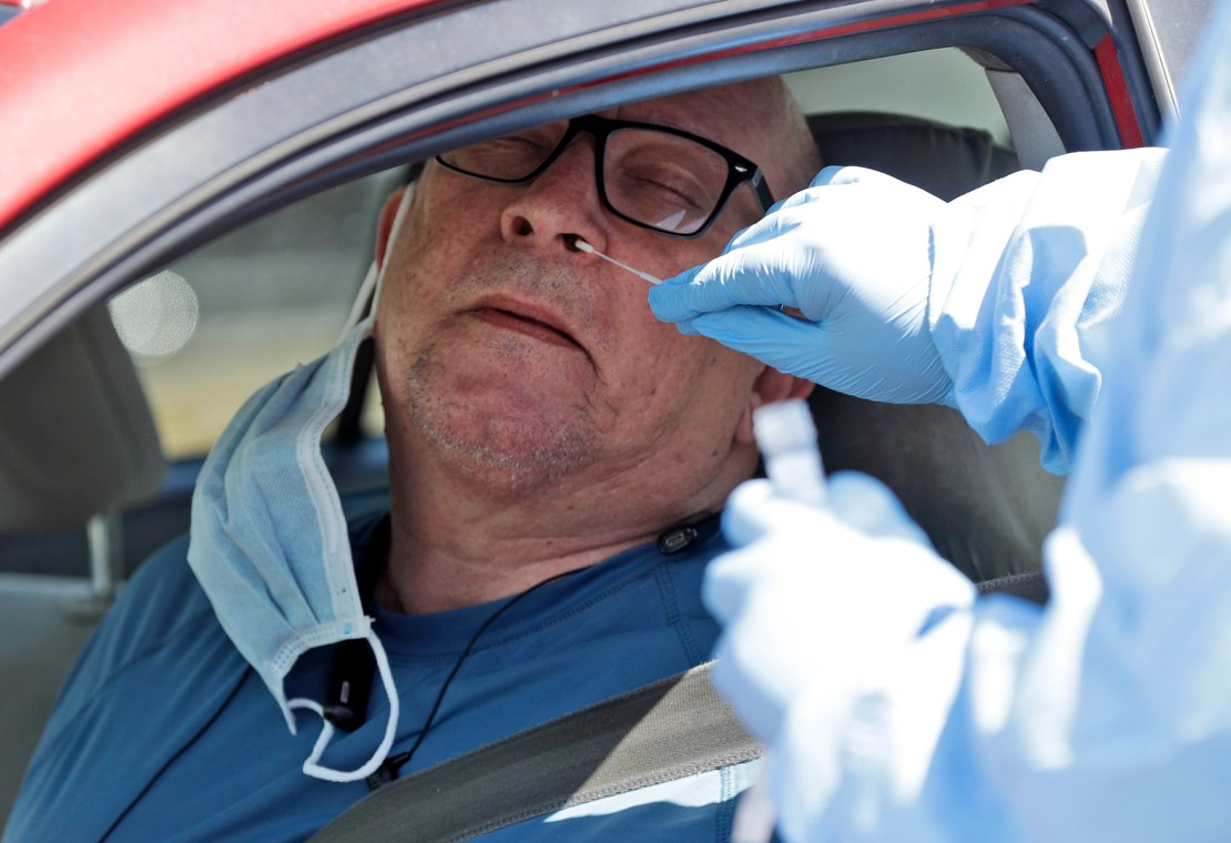 A medical worker inserting a small swab into a man's nose.
