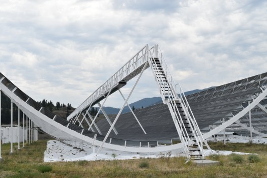 A large white and black satellite dish shaped like a half-pipe.