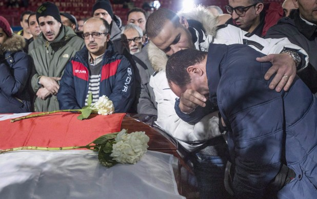 Mourners at a funeral are in tears and console each other as they lean over caskets
