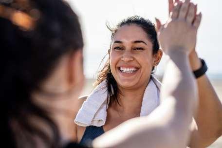 Personne souriante et donnant la main à une amie pendant qu'elle fait de l'exercice