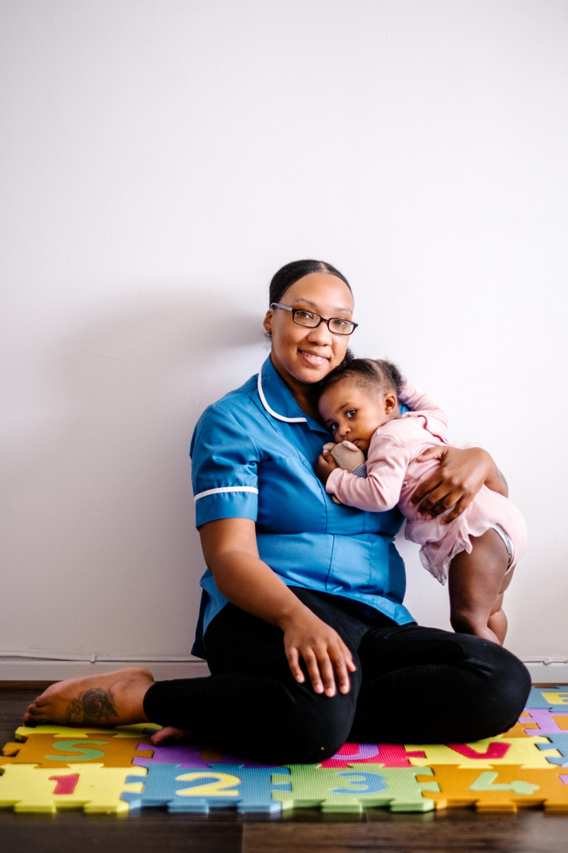 NHS midwife sitting on children's play mat while holding her daughter