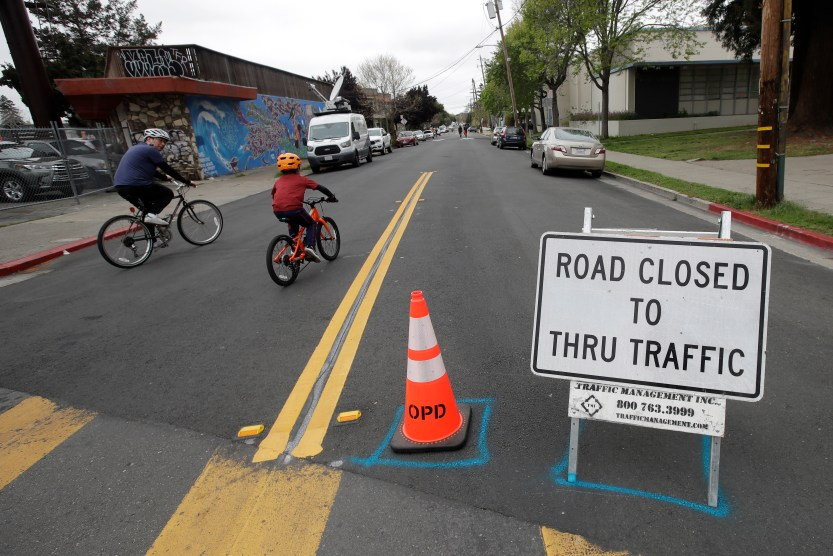 A man and child ride bikes past a street closure sign.