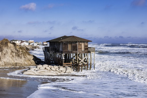 A storm-battered home on stilts in Nags Head sits out over the water with sandbags below it.