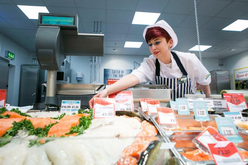 Female staffer at Morrisons selling meat and fish.