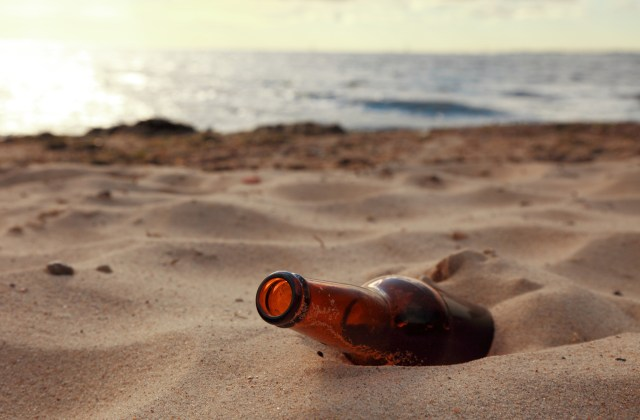 An empty beer bottle on a sandy beach.