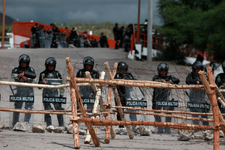 Soldiers in riot gear stand behind a fence wrapped with barbed wire.