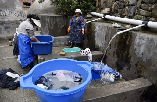 Deux femmes des peuples autochtones boliviens lavent leurs vêtements à un lavoir municipal utilisant de l'eau de pluie à La Paz, le 12 septembre 2019.