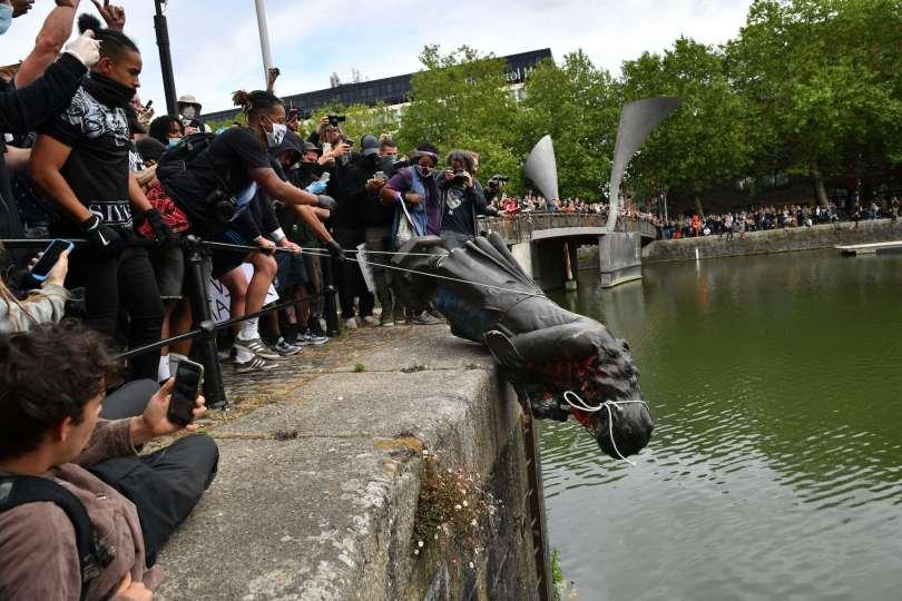 Protestors throw a statue into a river.
