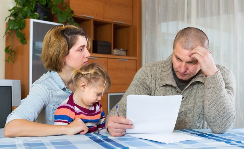 Couple with young child looks despondent and ponders paperwork.