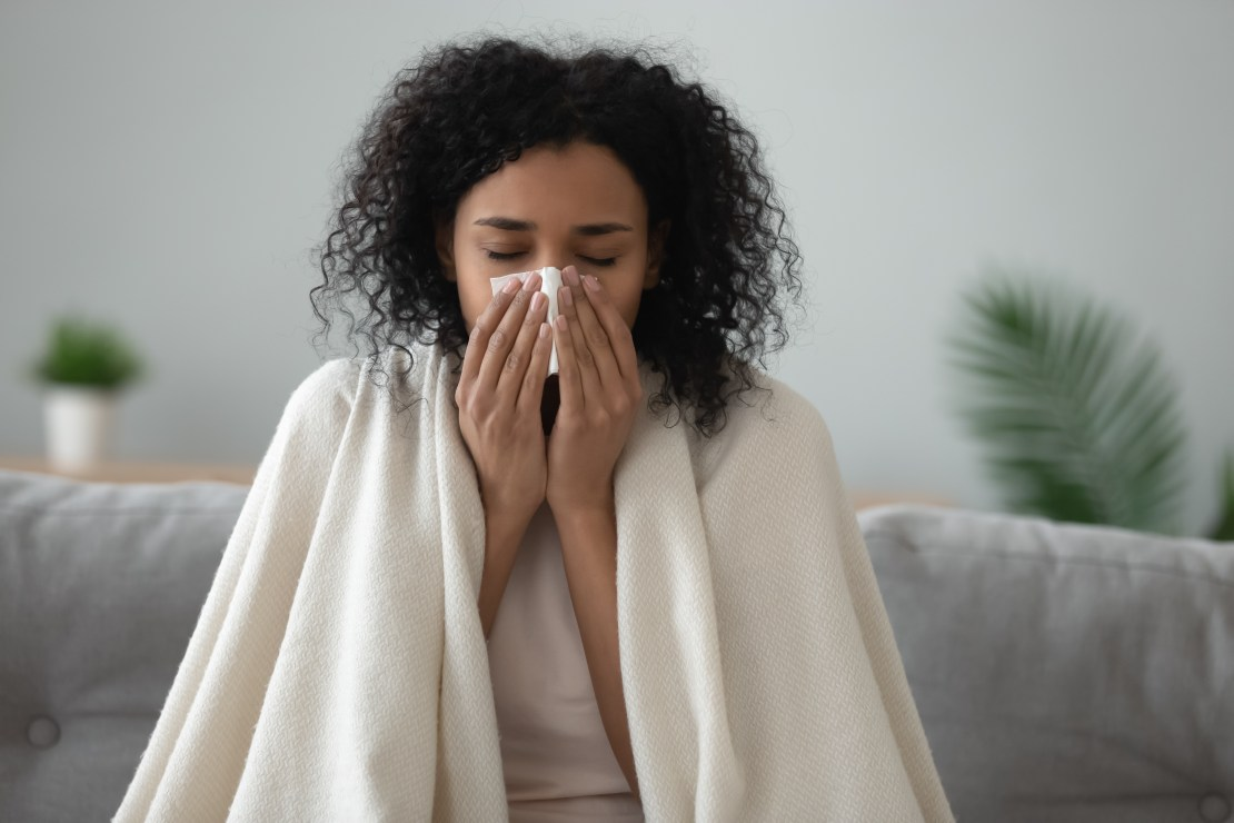 A woman with flu blowing her nose.