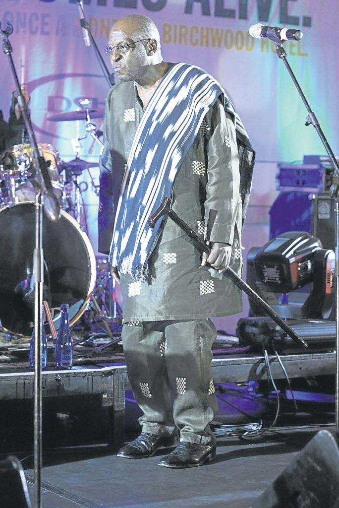 On a live music stage, a balding man in a tunic with cloth over his shoulder holds a walking stick. He is bathed in blue and silver stage light.