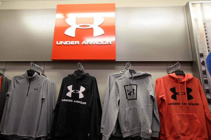 Under Armour hoodies hang on a rack.