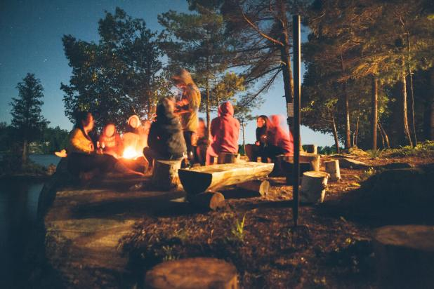 Group of people sit in forest near bonfire.
