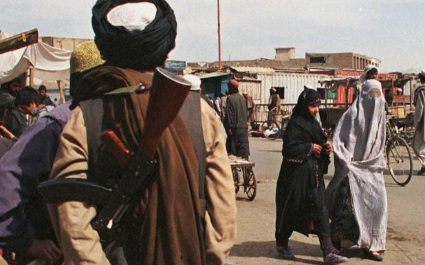 Two Afghan women wearing different styles of Burqas, pass by an armed fundamentalist Taliban militia soldier.