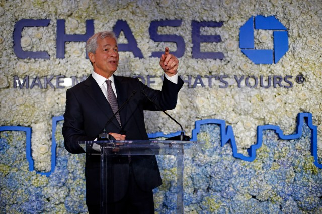 Jamie Dimon raises his left hand and points his index finger in a gesture as he stands in front of a glass lectern with the Chase logo behind him and an outline of a city in blue.