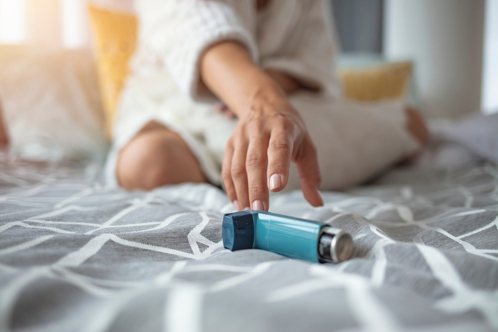 A woman with asthma reaching for her inhaler