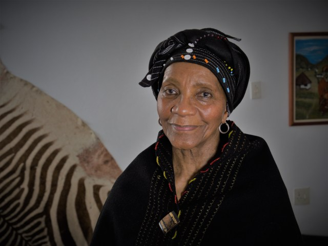 An elder woman smiles lightly as she looks into the camera, eyes warm and dressed in black, beaded traditional Xhosa attire, a zebra skin on the wall behind her.