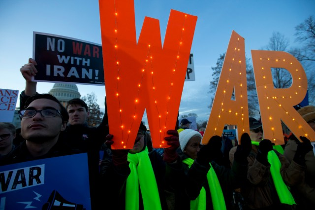 Demonstrators hold signs opposing war.