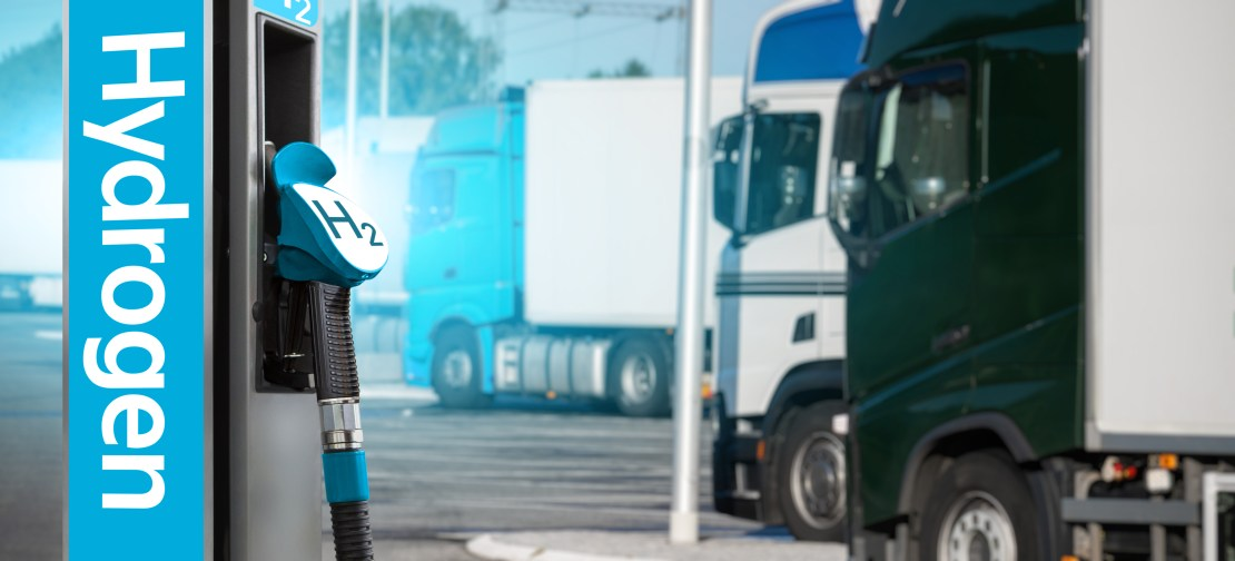 A hydrogen fuel pump at a service station with lorries in the background.