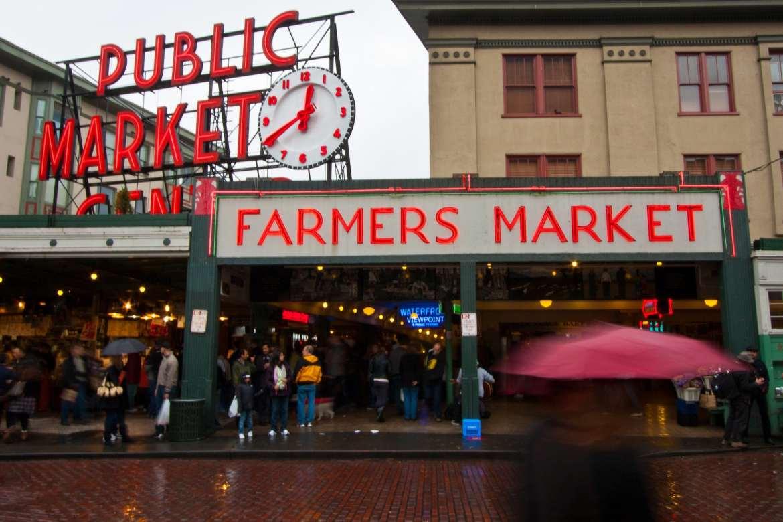 Shoppers enter market arcade on a rainy day.